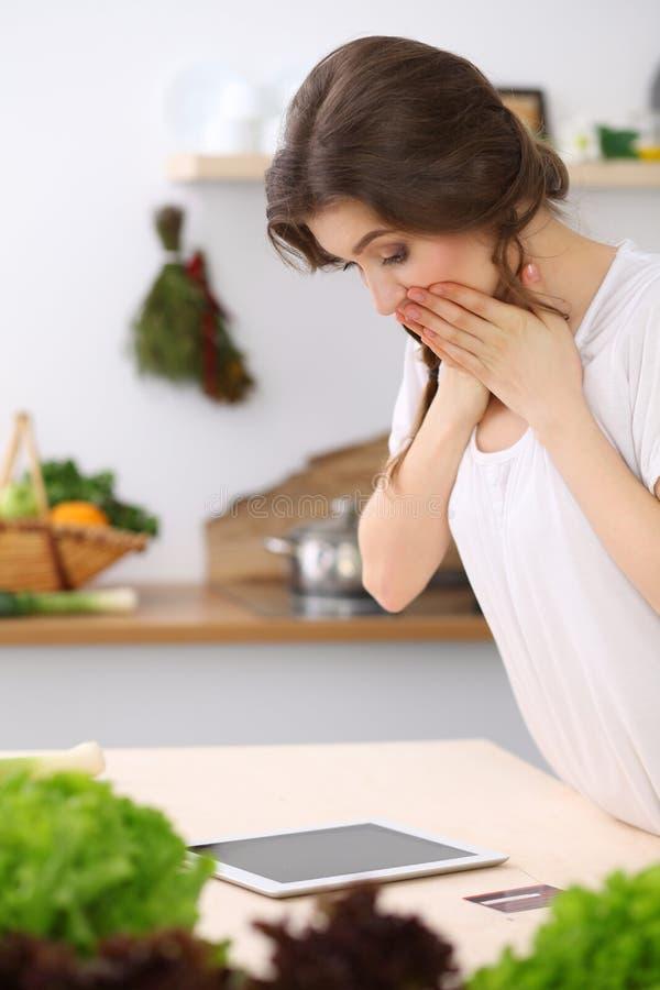 寻找烹调的少妇一份新的食谱在厨房里 主妇用片剂计算机做网络购物 图库摄影