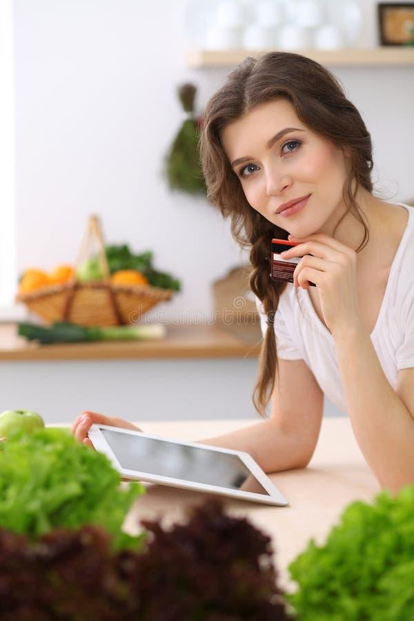寻找烹调的少妇一份新的食谱在厨房里 主妇用片剂计算机做网络购物 免版税库存照片
