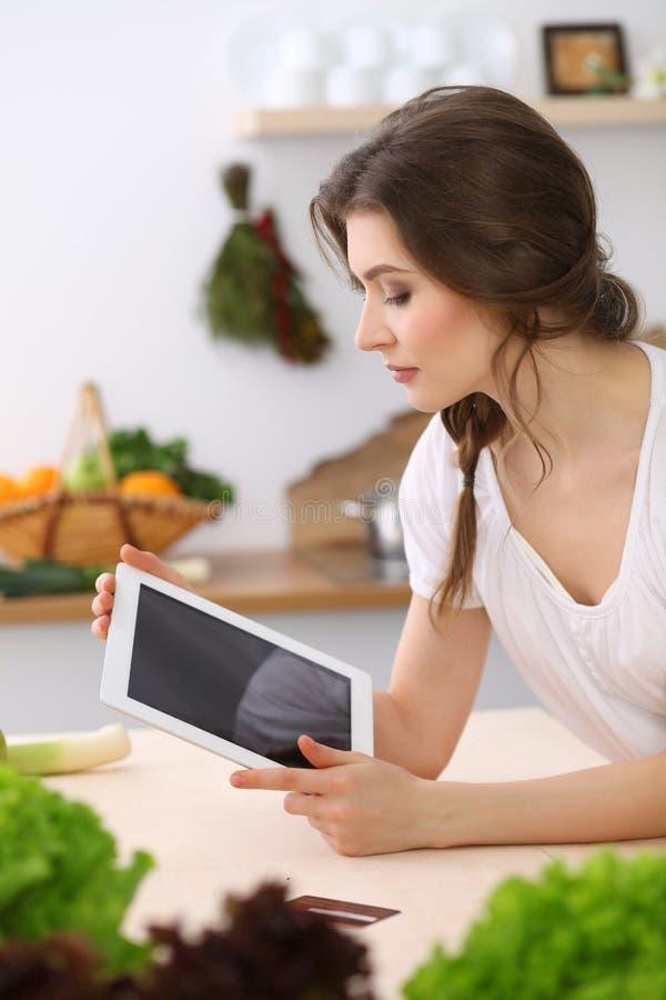 寻找烹调的少妇一份新的食谱在厨房里 主妇用片剂计算机做网络购物 免版税库存图片