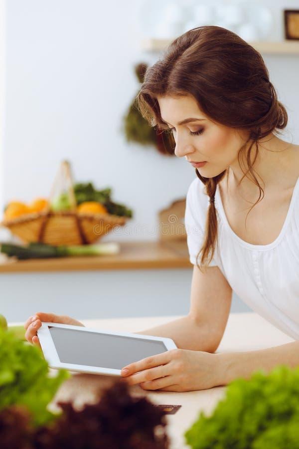 寻找烹调的年轻女人一份新的食谱在厨房里 主妇用片剂计算机做网络购物 免版税库存图片