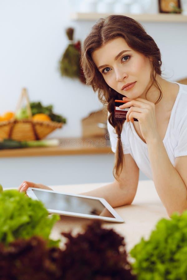 寻找烹调的年轻女人一份新的食谱在厨房里 主妇用片剂计算机做网络购物 库存照片