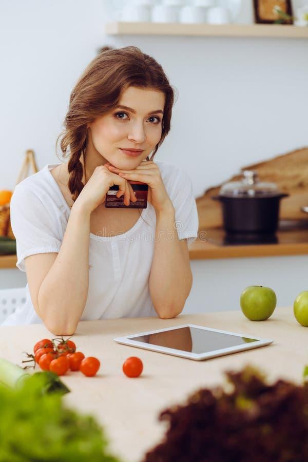 寻找烹调的年轻女人一份新的食谱在厨房里 主妇用片剂计算机做网络购物 图库摄影