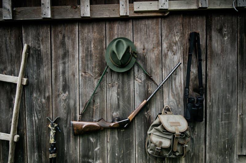 寻找的专业猎人设备 步枪、帽子,袋子和其他在木黑背景 图库摄影