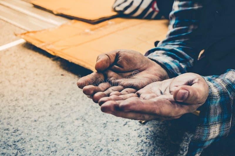 寻找金钱,从人类善良本性的硬币的男性叫化子手在街道走道的地板上 免版税库存照片