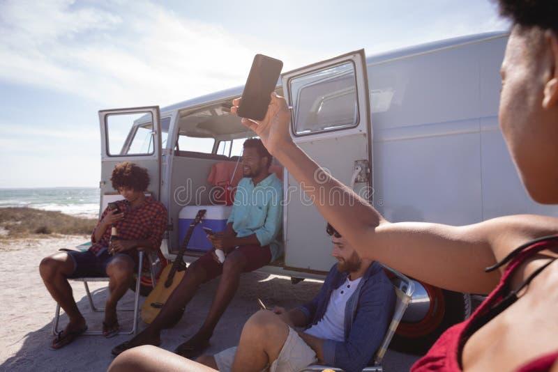 寻找WiFi的妇女的中央部位,当他的朋友在露营者货车附近时坐 图库摄影