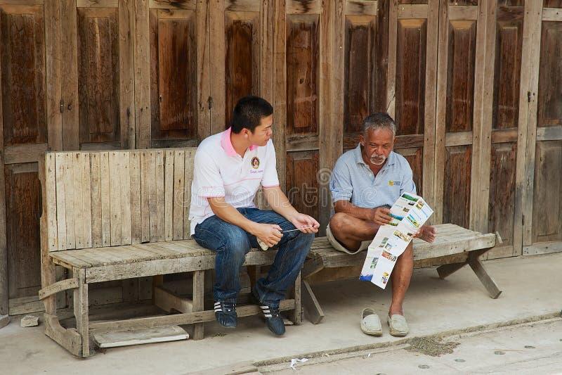 导游在城镇可汗,泰国坐在入口到其中一间旅舍 免版税库存照片