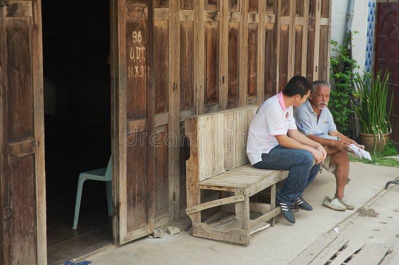 导游在城镇可汗,泰国坐在入口到其中一间旅舍 免版税图库摄影