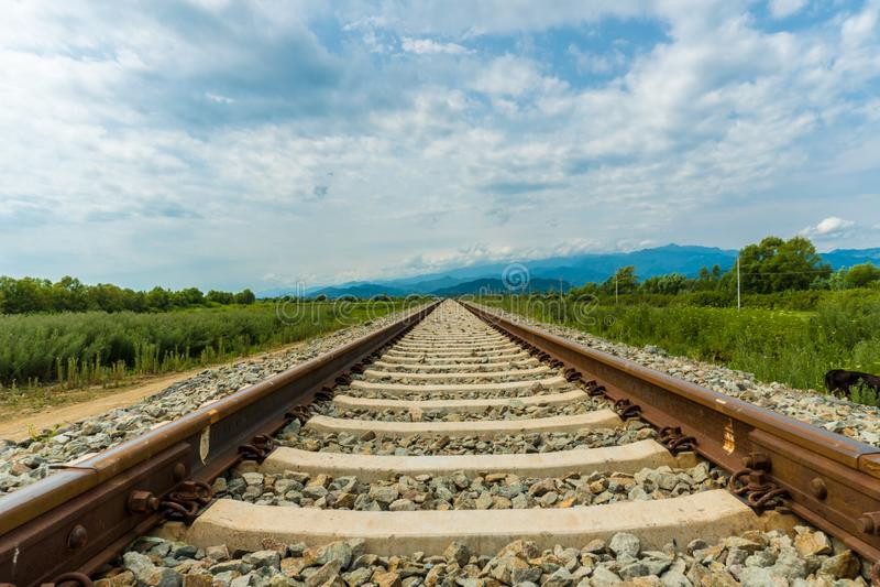 导致不尽的无限的铁轨 草甸风景和遥远的山 库存照片