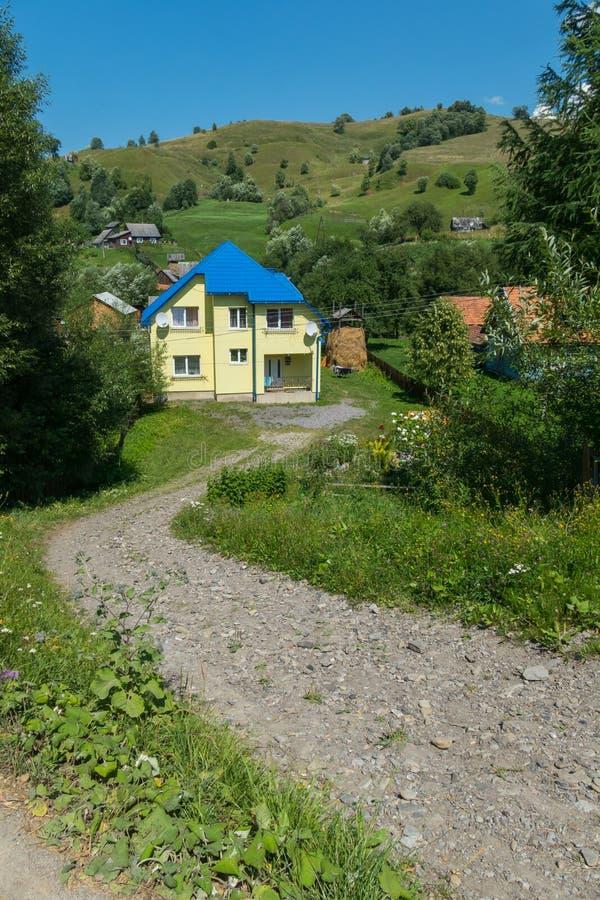 导致与一个蓝色屋顶的一个黄色村庄的山路反对一个高绿色倾斜 库存照片