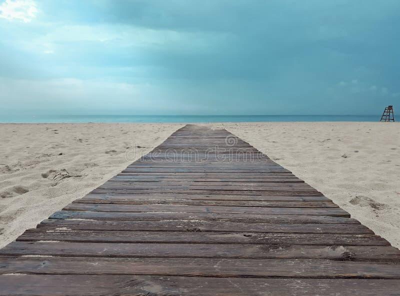 导致从海滩的木走道有一强烈的天空蔚蓝的海 免版税库存照片
