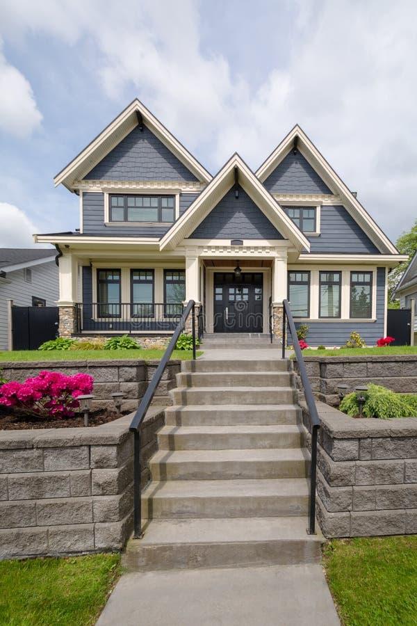 导致在前院的住宅房子入口的具体步鄹 在土地大阳台建造的豪华房子 免版税库存图片
