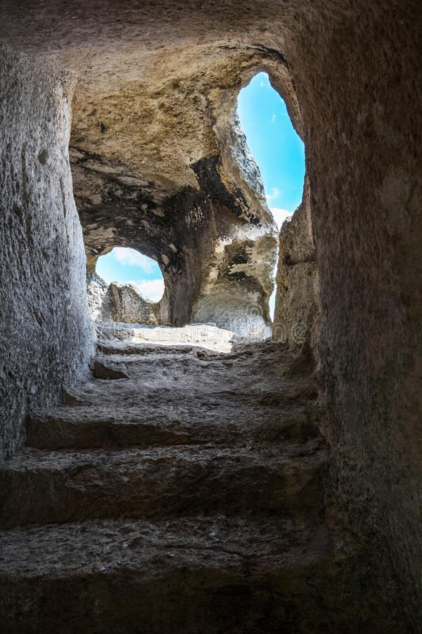 导致对在岩石段落的裁减的步 从窗口的轻的秋天,照亮洞 免版税库存照片