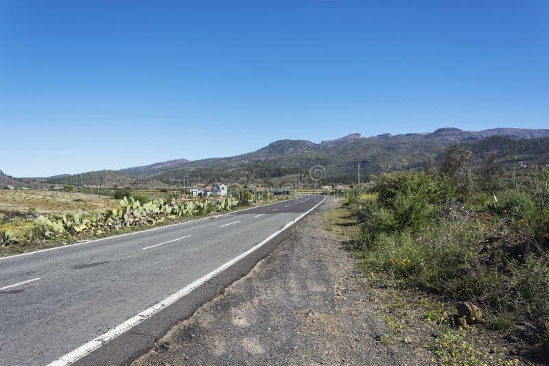 导致山的柏油路在一个晴天 山l 库存图片