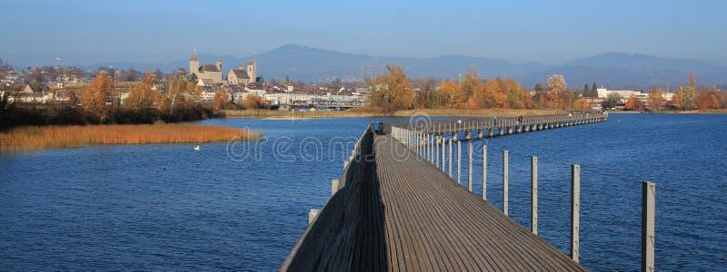 导致拉珀斯维尔的木板走道 蓝色湖Obersee和金黄tr 库存照片