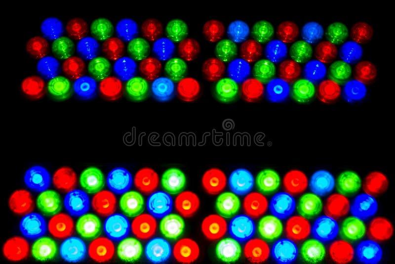 导致的光 照明的多彩多姿的电灯泡 色的电灯泡纹理在黑暗的 免版税库存照片