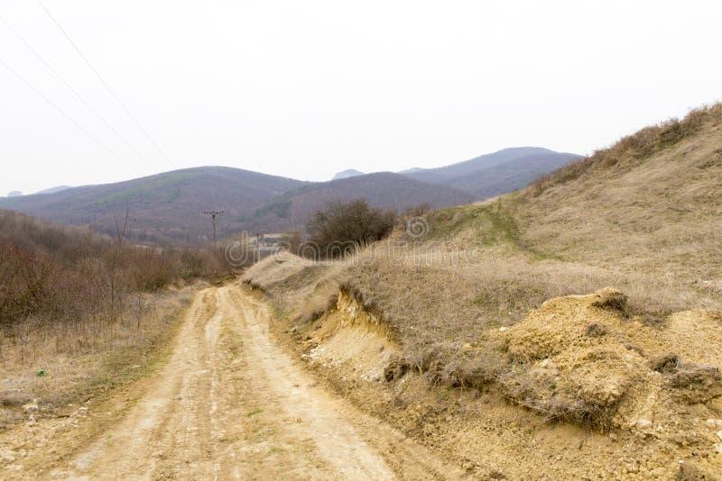 导致脊柱村庄和山风景的越野路 免版税图库摄影