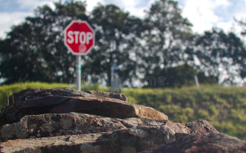 导致被弄脏的背景的岩石墙壁包含停车牌 库存图片