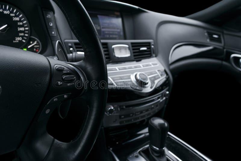 导航在一辆现代汽车的方向盘按有黑穿孔的皮革内部的 现代汽车内部细节 免版税库存照片