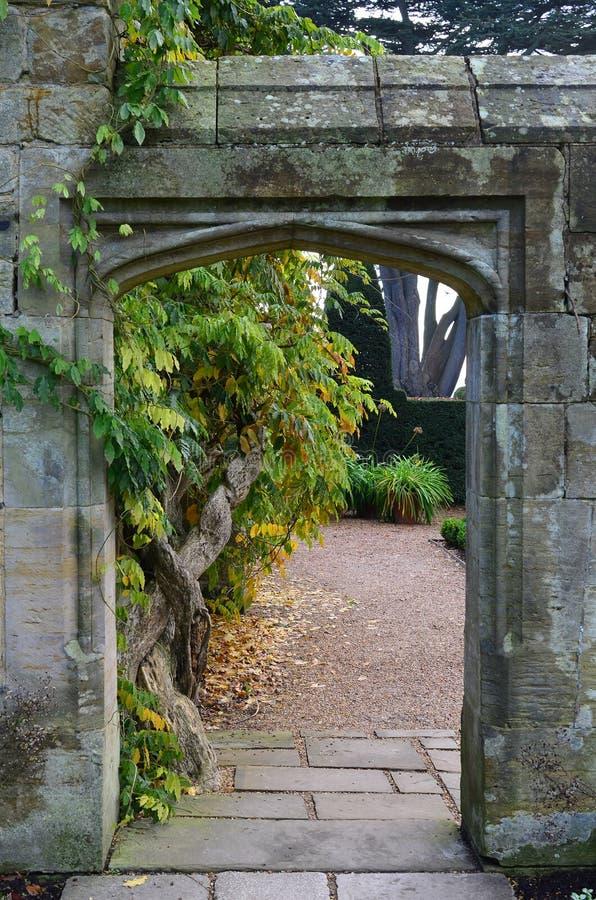 导致一个规则式园林的石入口 库存照片