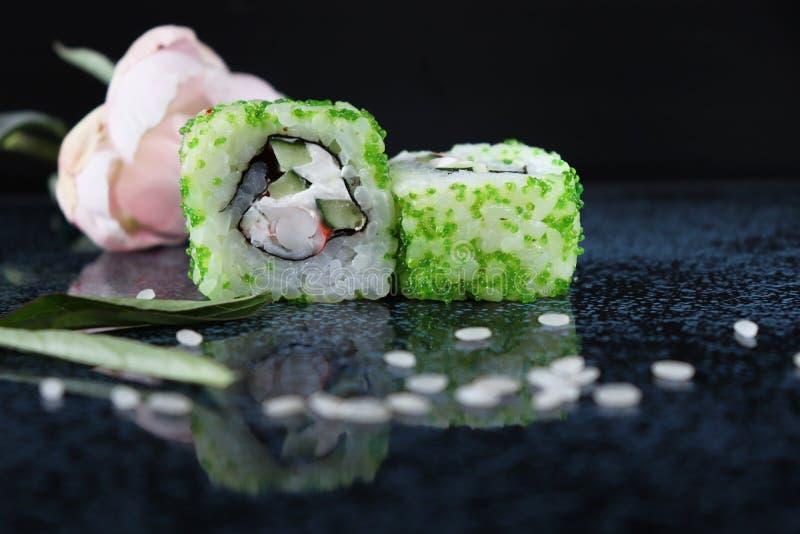 寿司Ð iece用鱼子酱 绿色地产 绿色鱼子酱 桌的光滑的表面上的寿司 免版税库存照片