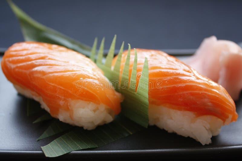 寿司冠上在黑背景的nigiri用米和neta三文鱼鱼 库存照片