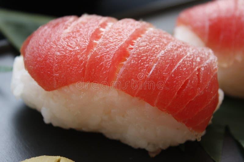 寿司冠上在黑背景的nigiri用米和neta三文鱼鱼 库存图片