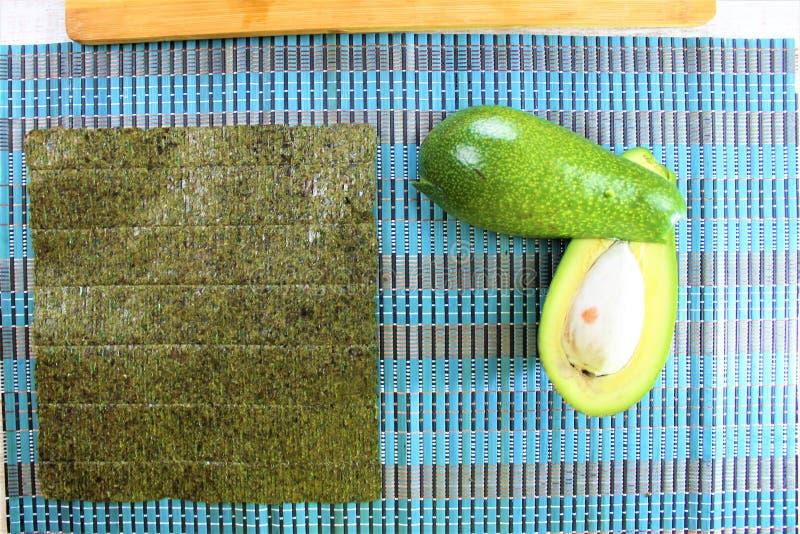 寿司准备在厨房,新鲜的成份绿色鲕梨用海草切成了两半,并且白色烹调了在木裁减的米 库存照片