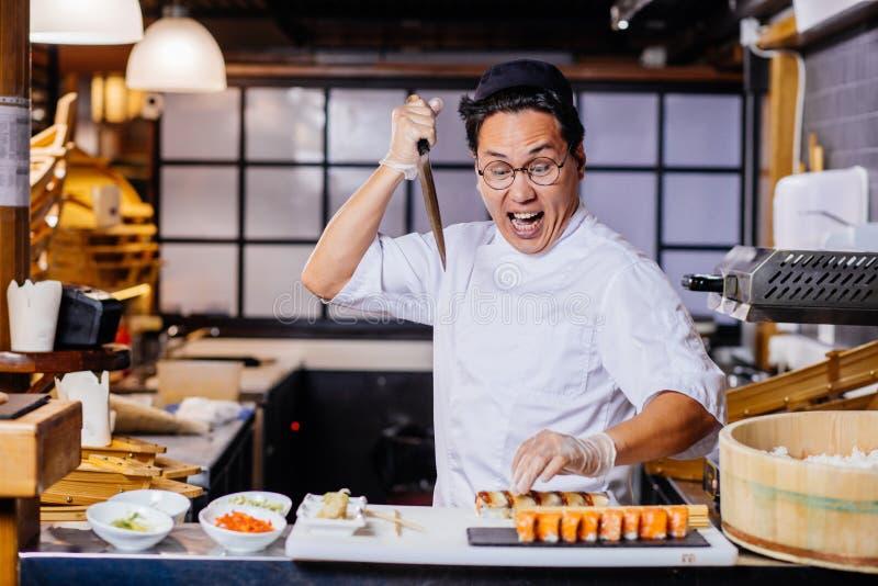 寿司凶手  滑稽的厨师获得乐趣在寿司咖啡馆 免版税库存照片