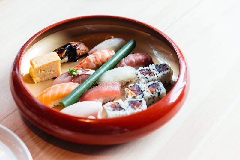 寿司午餐集合包括三文鱼,金枪鱼、乌贼、虾、Hamachi、乌纳吉和Tamagoyaki在红色碗服务 库存图片