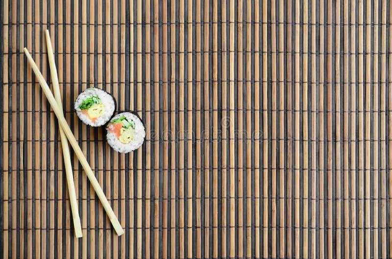 寿司卷和木筷子在一张竹秸杆serwing的席子说谎 亚洲食物炒饭传统蔬菜 顶视图 平的被放置的简单派射击 库存图片
