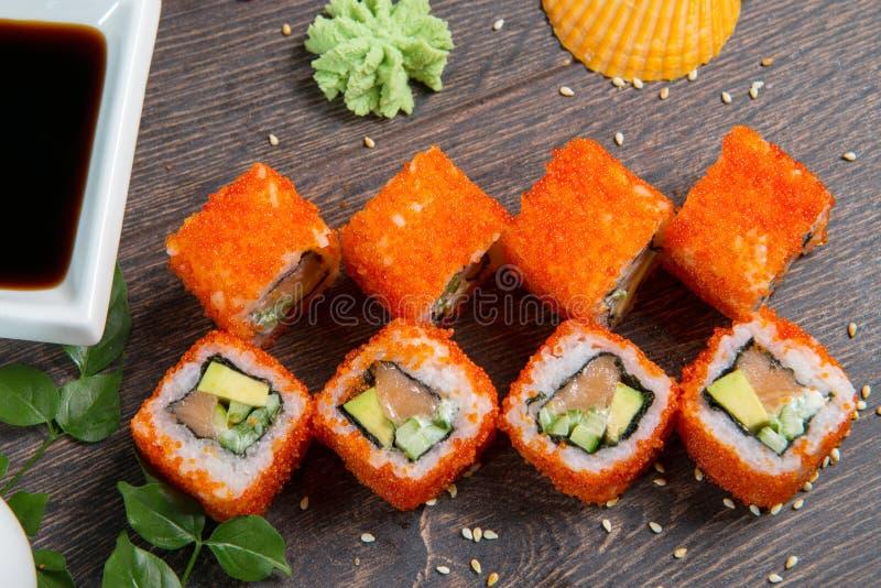 寿司卷和鱼子酱在黑木桌上 日本食物 免版税库存照片