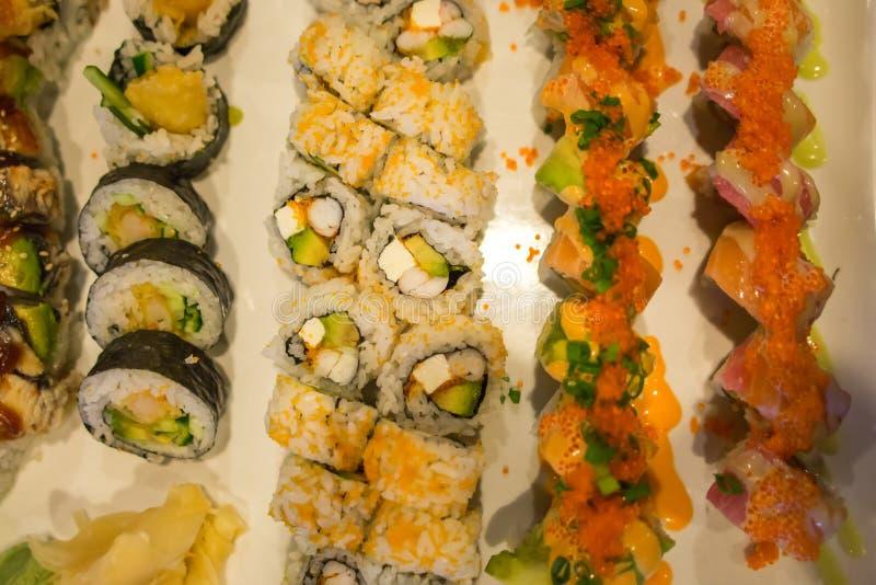 寿司卷品种在饭桌上的 库存图片