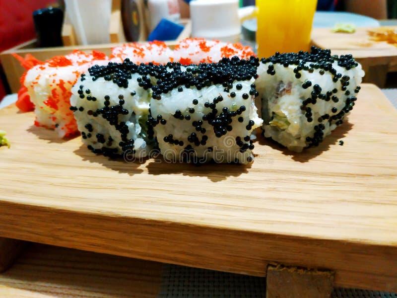 寿司卷日本食物在餐馆 加利福尼亚寿司卷设置了与三文鱼、菜、飞鱼獐鹿和鱼子酱特写镜头 免版税库存照片