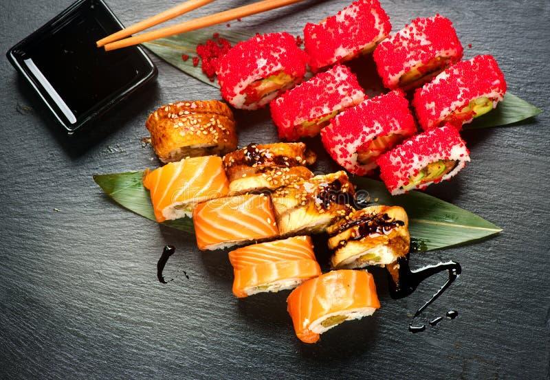 寿司卷特写镜头 日本食物在餐馆 滚动用三文鱼、鳗鱼、菜和飞鱼鱼子酱 免版税库存照片