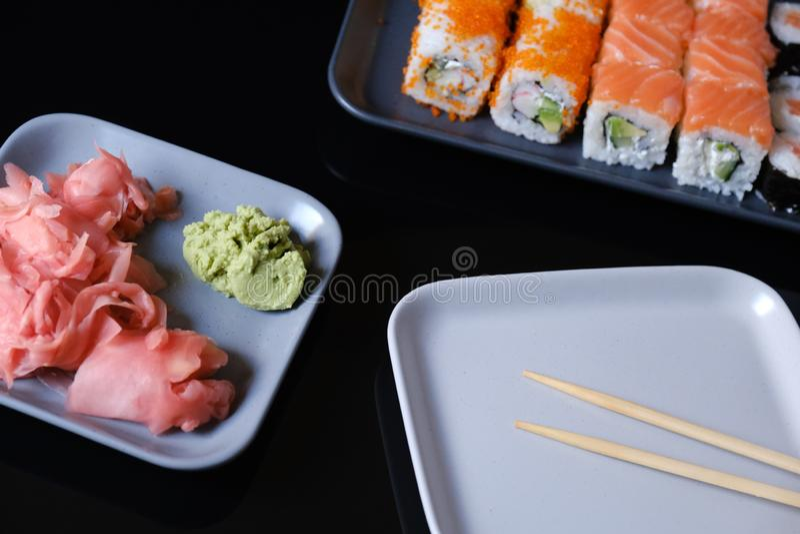 寿司卷用海鲜和酱油、山葵和姜 与三文鱼的寿司卷在一张灰色板材和黑桌 库存照片