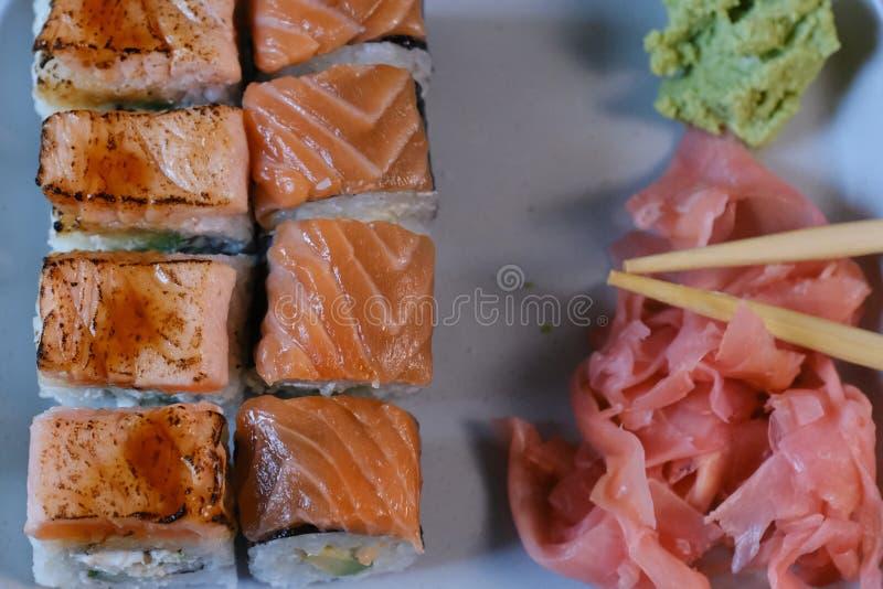 寿司卷用海鲜和酱油、山葵和姜 与三文鱼的寿司卷在灰色背景 图库摄影
