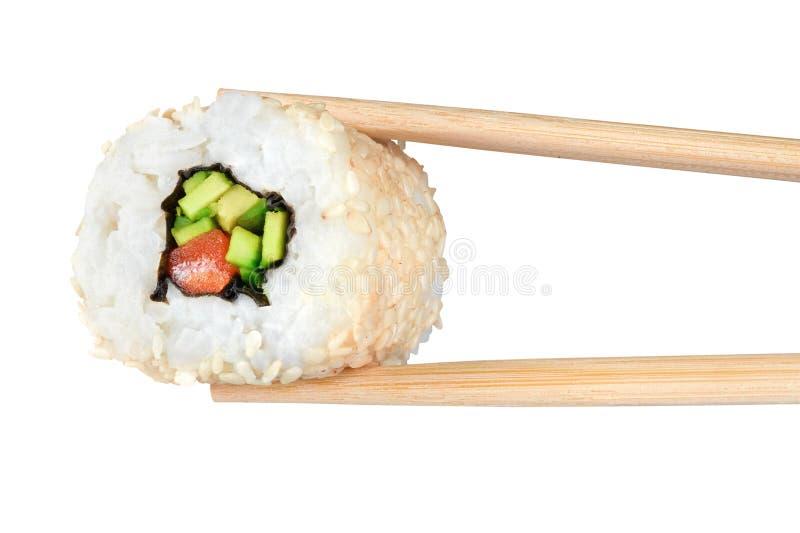 寿司卷用鲕梨、三文鱼和芝麻籽 筷子 免版税图库摄影