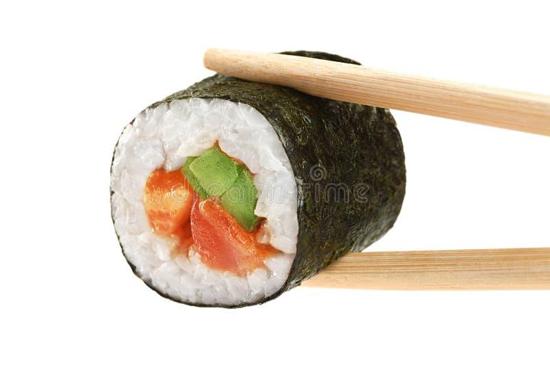 寿司卷用鲕梨,三文鱼和辣调味汁 筷子 免版税库存照片