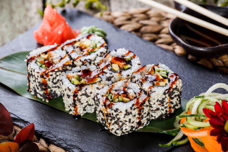 寿司卷设置了与虾天麸罗、黄瓜、鲕梨和芝麻在黑石头在竹席子,选择聚焦 库存图片