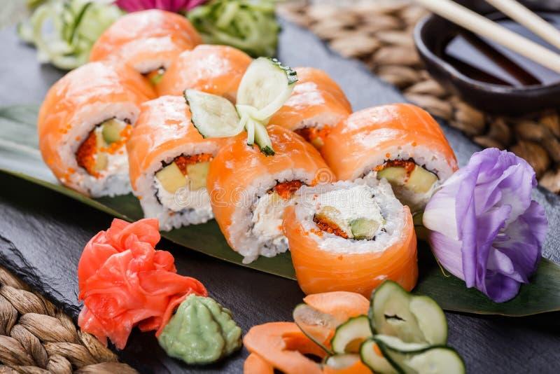 寿司卷设置了用三文鱼,乳脂干酪、红色鱼子酱、鲕梨和山葵在黑石头在竹席子,选择聚焦 免版税库存照片