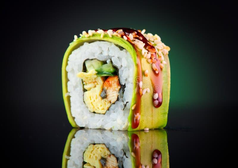 寿司卷黑背景 寿司卷用鳗鱼、豆腐、菜和鲕梨特写镜头 图库摄影