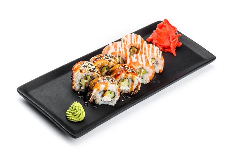 寿司卷-梅基寿司由三文鱼,熏制的鳗鱼、黄瓜、鲕梨和奶油奶酪制成在黑色的盘子 免版税图库摄影