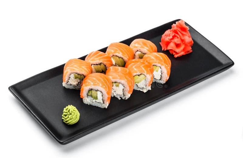 寿司卷-梅基寿司由三文鱼,鲕梨和奶油奶酪制成在黑色的盘子被隔绝在白色背景 库存图片