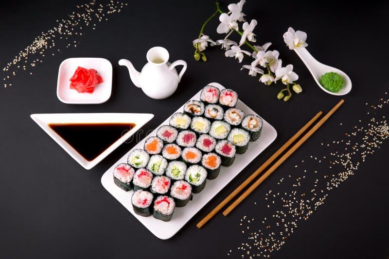 寿司菜单 日本食物 套与三文鱼,金枪鱼, chuka,黄瓜,鲕梨,乳酪,鳗鱼,虾,螃蟹棍子, tobiko鱼子酱的maki 库存图片