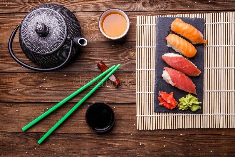 寿司集合在灰色石板岩服务用酱油、灰色茶壶和茶 图库摄影