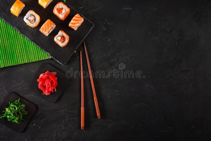 寿司集合生鱼片和寿司卷在石板岩服务 免版税库存图片