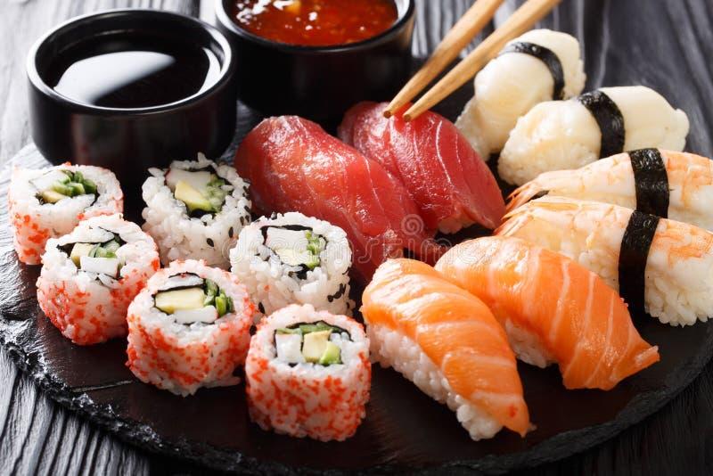 寿司食物品种  nigiri、maki、uramaki和卷与金枪鱼、三文鱼和虾 与生鱼片和米的亚洲食物 水平 图库摄影