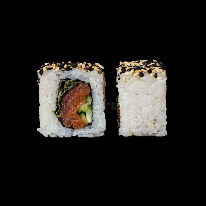 寿司 与熏制鲑鱼、lola罗斯沙拉、黄瓜和油煎的芝麻的卷,隔绝在黑背景中 免版税库存图片