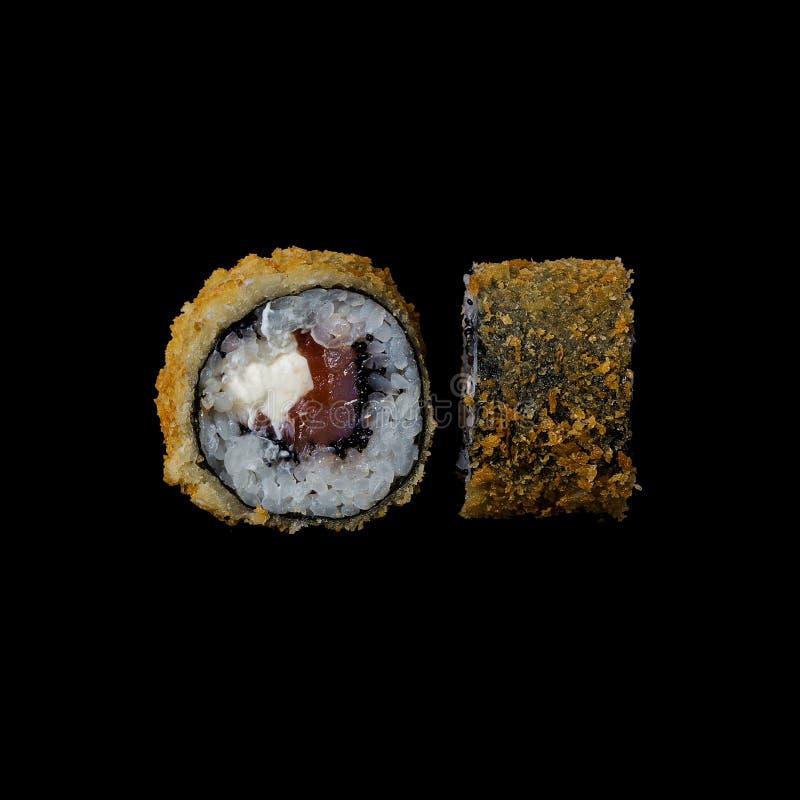 寿司 与鳗鱼天麸罗和奶油奶酪的卷,隔绝在黑背景中 免版税库存照片