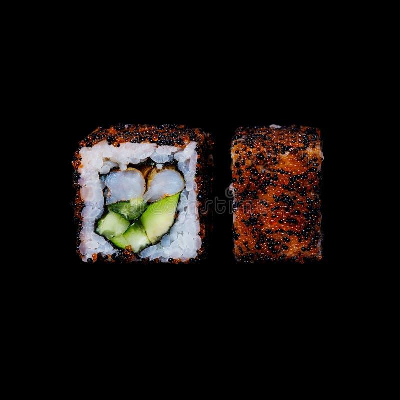 寿司 卷用油煎的铁锅虾、黄瓜、鲕梨和tobiko,隔绝在黑背景中 免版税图库摄影